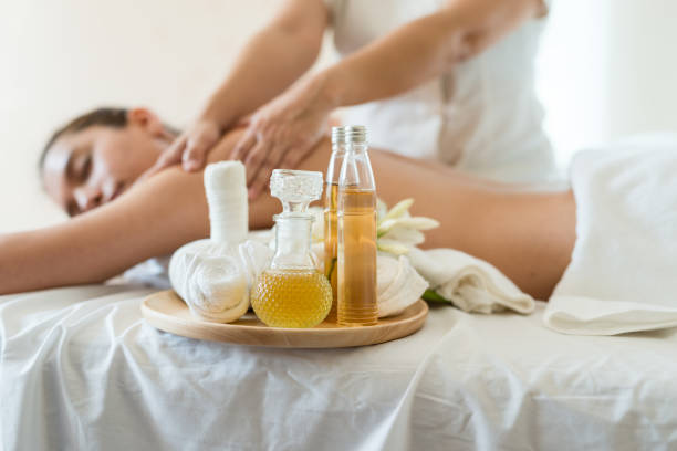 bottle of essential oil on a wooden tray. background young beautiful asian woman relaxing in the spa massage - thai massage stock photos and pictures