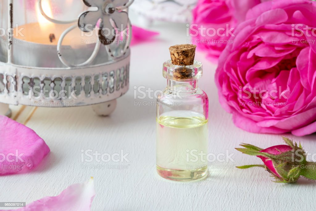 A bottle of essential oil with fresh rose flowers zbiór zdjęć royalty-free