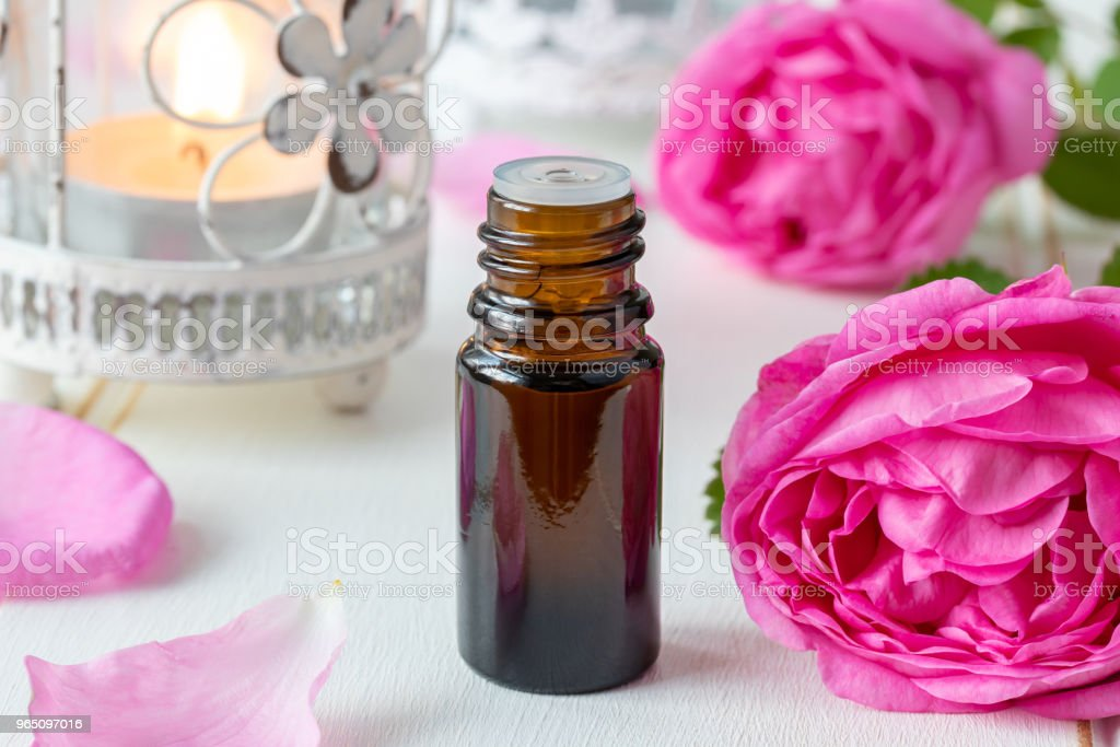 A bottle of essential oil with fresh rose flowers zbiór zdjęć royalty-free