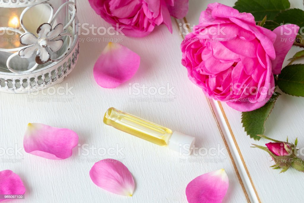 A bottle of essential oil with fresh rose flowers royalty-free stock photo