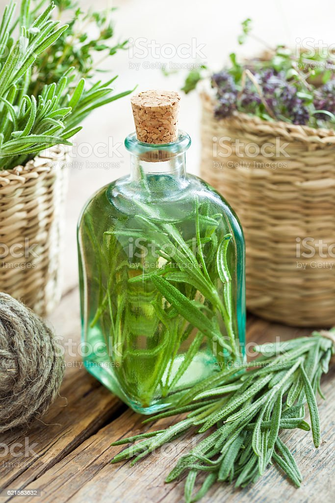 Bottle of essential rosemary oil or infusion and healing herbs stock photo