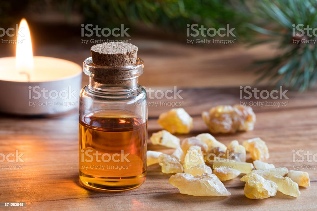 A bottle of frankincense essential oil with frankincense resin stock photo