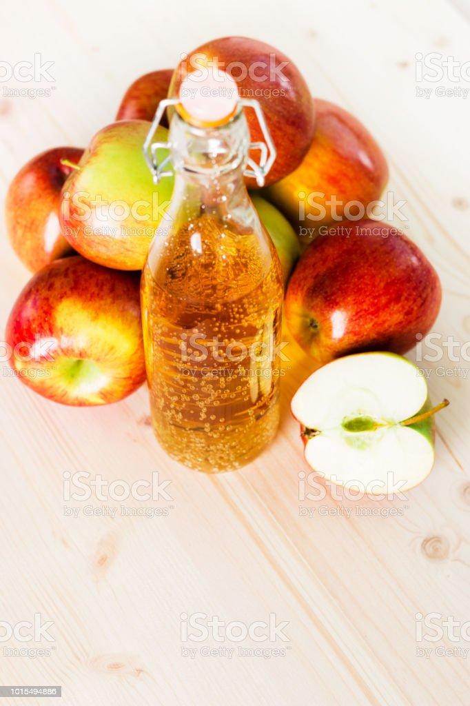 Bottle of fresh apple cider and half apple near autumn apples stock photo