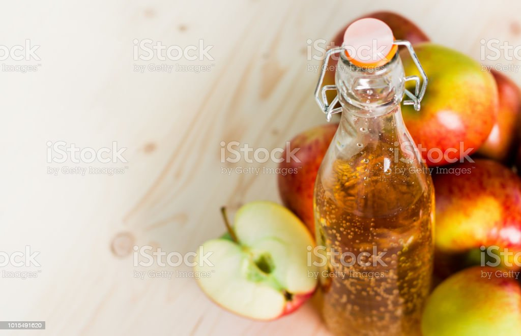 Bottle of fresh apple juice and half apple near autumn apples stock photo