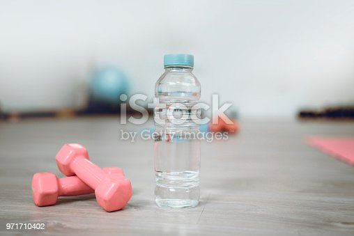 A Bottle Of Fresh Water And Dumbbells In Gym