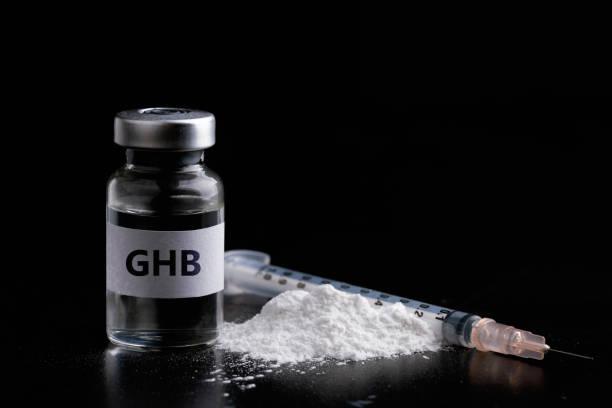 fles ghb met een spuit in zwarte achtergrond. gevaarlijke drug vrouwen - ketamine stockfoto's en -beelden