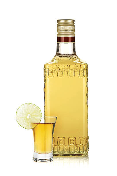 Bottle of gold tequila and shot with lime slice Bottle of gold tequila and shot with lime slice. Isolated on white background tequila shot stock pictures, royalty-free photos & images