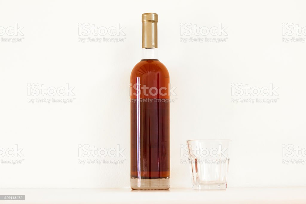 Bottle of Golden Brandy/Dessert Wine/Malvasia/Cognac, Classic Tumbler, White Background stock photo