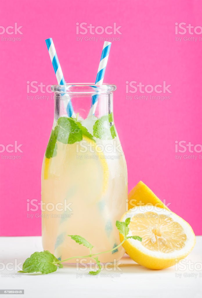 Bottle of homemade lemonade with mint, ice, lemons, paper straws and bright purple background stock photo