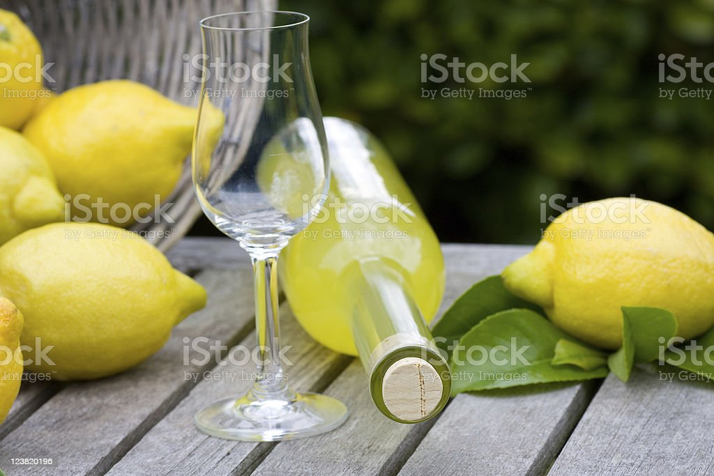 Bottle of Limon cello and wine glass with lemons stock photo