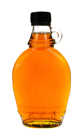 A full bottle of real maple syrup on a white background.