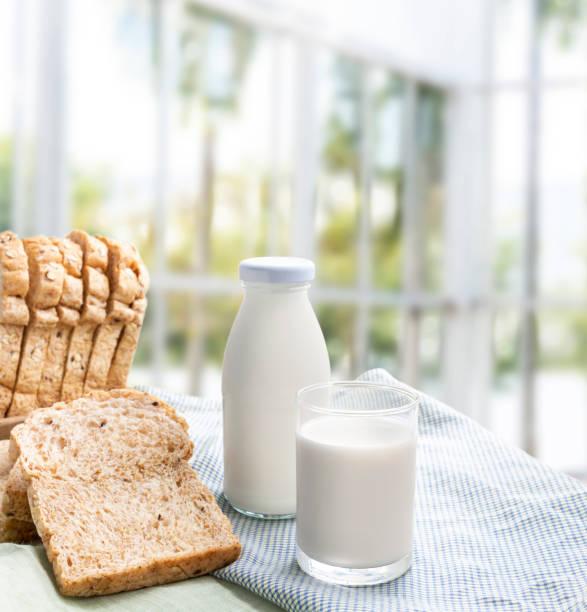 우유 병으로 우유의 유리 썬 천으로 빵 실내 음식과 건강 개념에 대 한 배경. 와 텍스트 복사 공간. 스톡 사진