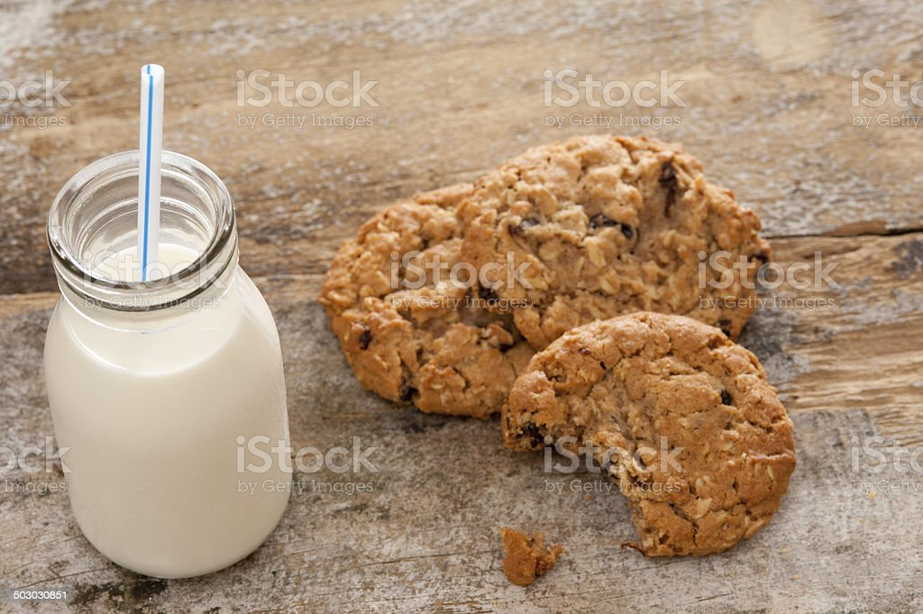Bottle of milk with half eaten cookies stock photo