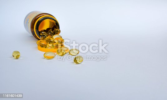 A bottle of oil capsules scattered with omega 3 or vitamin D. Oil gold color capsules isolated on white background. Healthy life concept with copy space for your text. Healthy supplement pills.