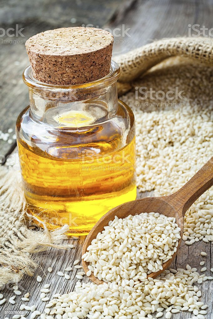 bottle of oil sesame seeds in sack on old table stock photo