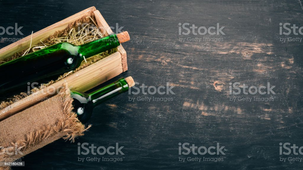 A bottle of old red wine in a box. On a black wooden background. Top view. Copy space for your text. stock photo