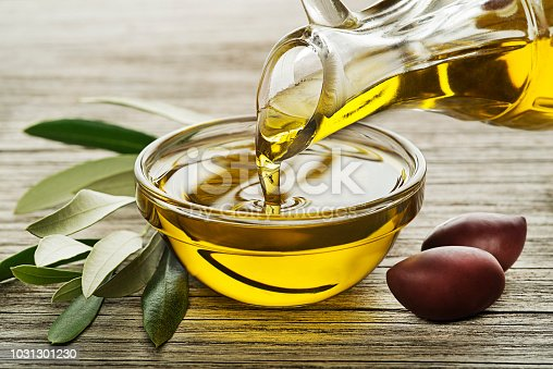 Bottle of Olive oil pouring in a glass bowl with olives and branch