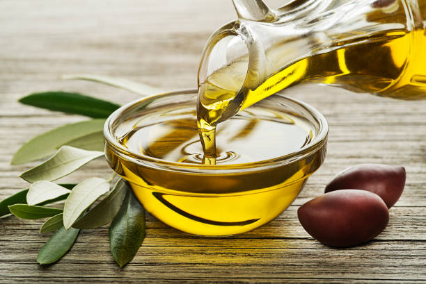 Bottle of Olive oil pouring close up Bottle of Olive oil pouring in a glass bowl with olives and branch olive oil stock pictures, royalty-free photos & images