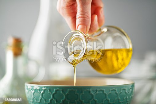 Bottle of virgin olive oil pouring to bowl close up