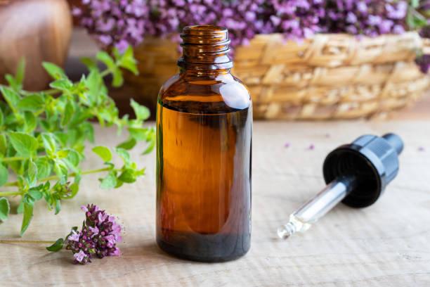 una botella de aceite esencial de orégano fresco orégano floreciente - orégano fotografías e imágenes de stock