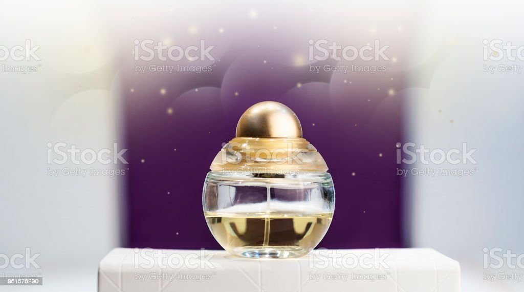 bottle of perfume on a stand on a purple background stock photo