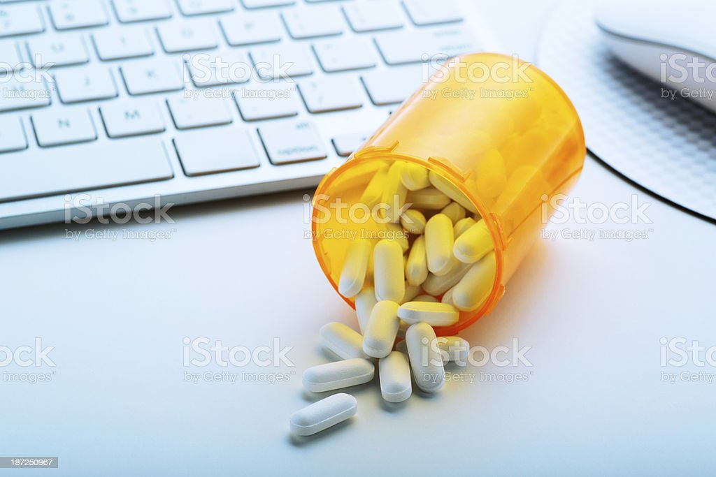 Bottle of Pills by a Computer royalty-free stock photo