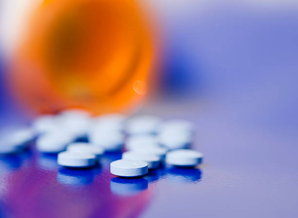 Bottle of pills on blue background Bottle of pills on blue background generic drug stock pictures, royalty-free photos & images