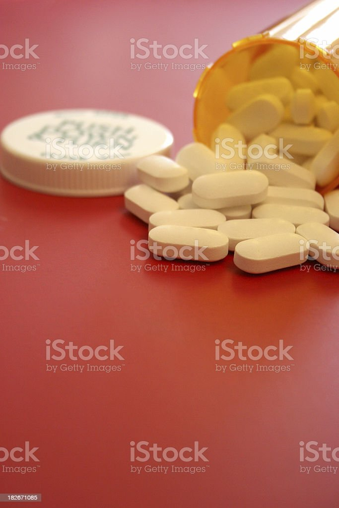 Bottle of Pills on Red Vertical royalty-free stock photo