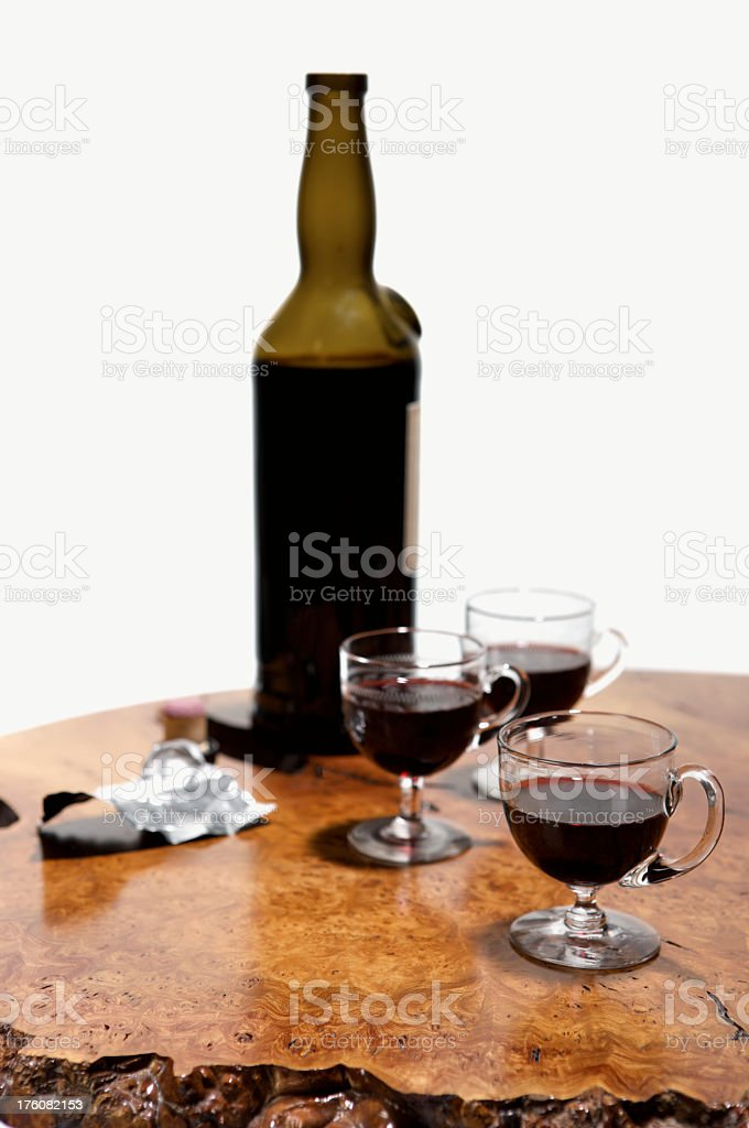 Bottle of Port with three filled glasses on wooden table stock photo