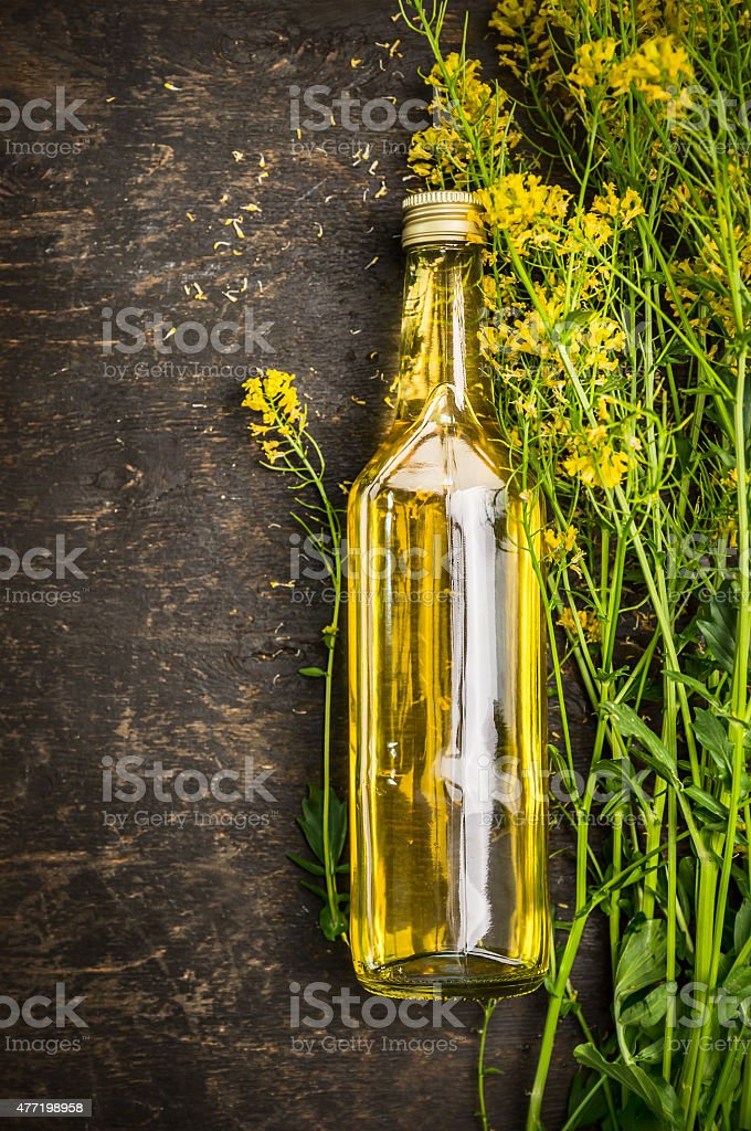 Bottle of Rape oil on rustic wooden background, top view stock photo