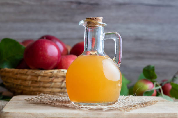 A bottle of raw unfiltered apple cider vinegar A bottle of raw unfiltered apple cider vinegar with fresh apples apple cider vinegar stock pictures, royalty-free photos & images