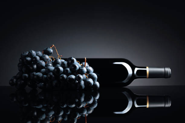 Bottle of red wine and a bunch of grapes on a black reflective background. stock photo