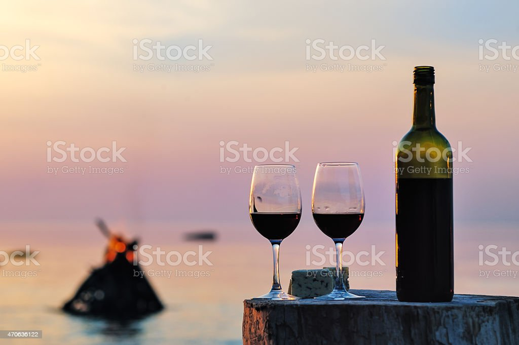 Bottle of red wine and two glasses with cheese on tree stump stock photo