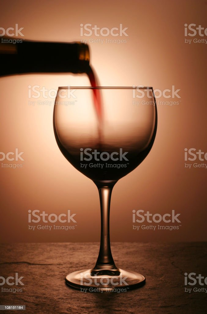 Bottle of Red Wine Being Poured into Glass royalty-free stock photo