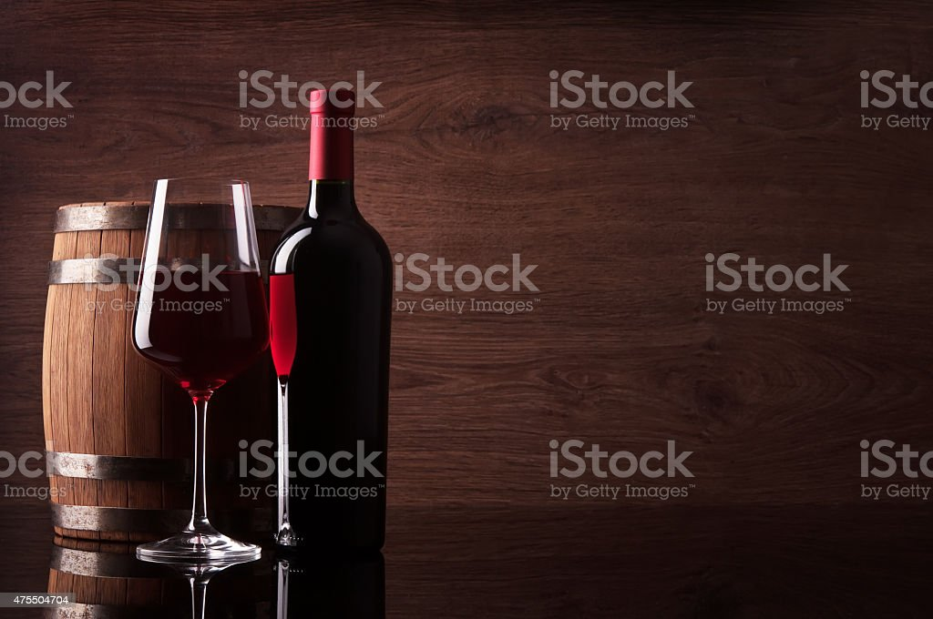 Bottle of red wine, glass and barrel on wooden background stock photo