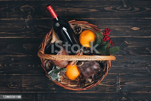 Bottle of red wine in Christmas gift basket. Mulled wine with oranges, cups and fir-tree ornaments in box. Top view