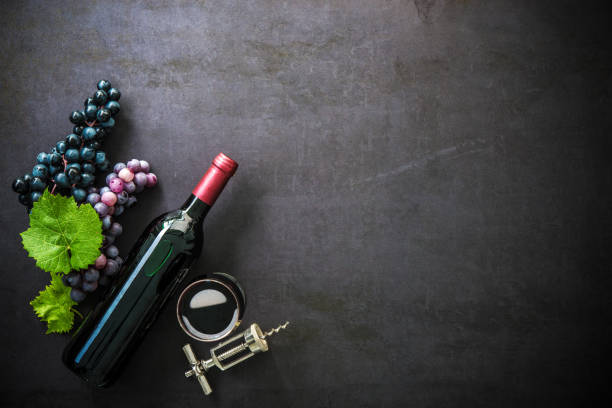 Bottle of red wine, wineglass and grapes stock photo