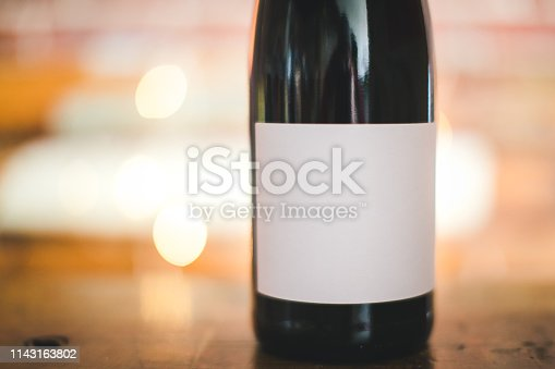Bottle of red wine with a white blank label and string light bokeh on background