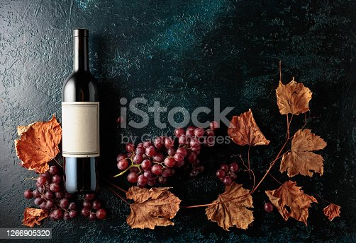 Bottle of red wine with ripe grapes and dried up vine leaves. Old dark blue background. On a bottle old empty label. Copy space, top view.