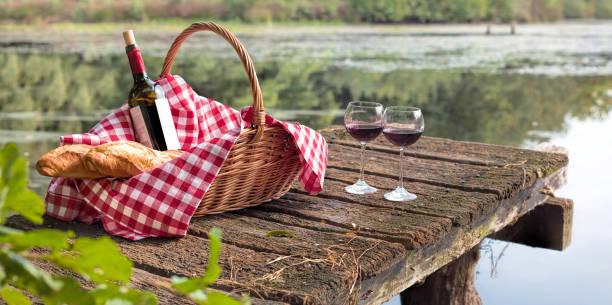 Flasche Rotwein mit zwei Gläsern und Korb mit frischen Baguettes auf hölzernen Steg am See – Foto