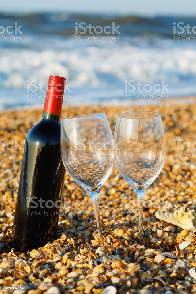 Bottle of red wine with two wineglass on the beach close up