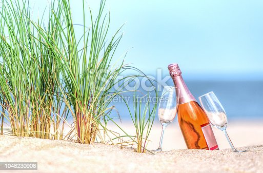 Bottle of rose colored champagne with drinking glasses on beach.