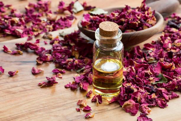 Bottle of rose essential oil with dried rose petals on a wooden picture id899747894?b=1&k=6&m=899747894&s=612x612&w=0&h=y0q9dfdlk6r cdhd0xjwa5bcyqzpmcv9acwssf0zc4m=