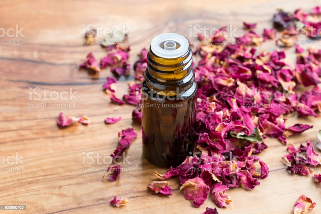 A Bottle Of Rose Essential Oil With Dried Rose Petals Stock Photo -  Download Image Now