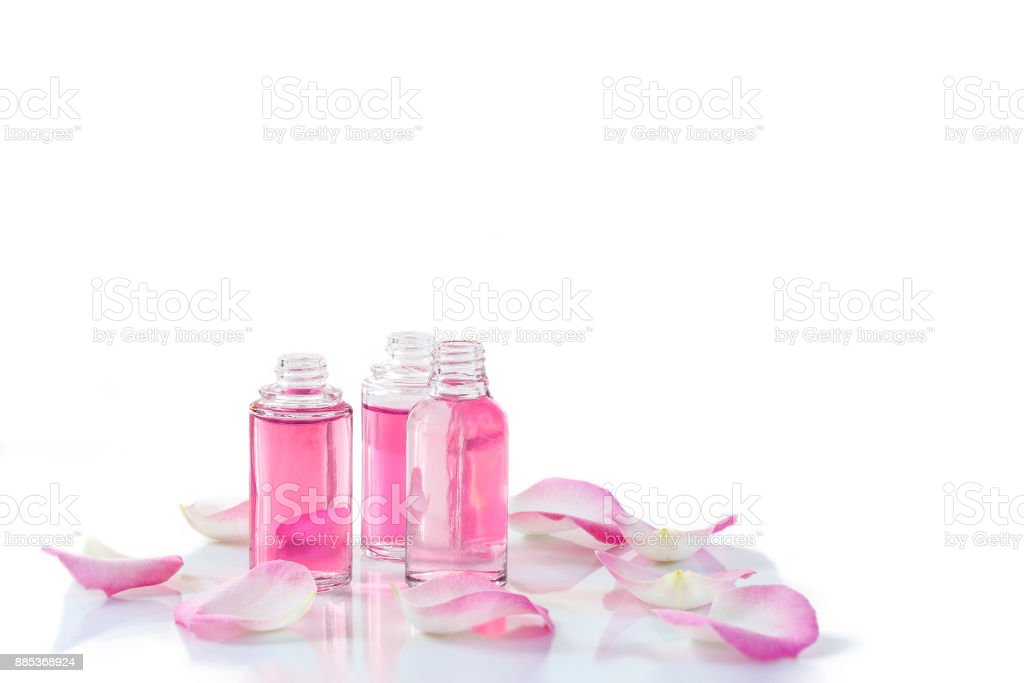 A bottle of rose essential oil with rose petals on white background stock photo