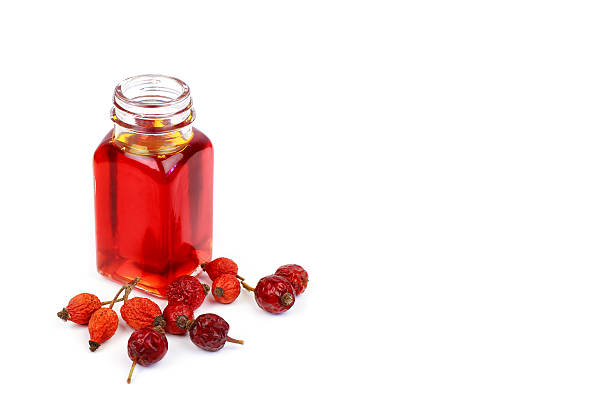 Bottle of rose hip oil on white background Bottle of rose hip oil on white background wild rose stock pictures, royalty-free photos & images