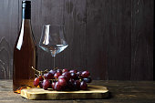 A bottle of rose wine stands on a wooden table, next to an empty glass and a bunch of grapes on a wooden board. Place for text.