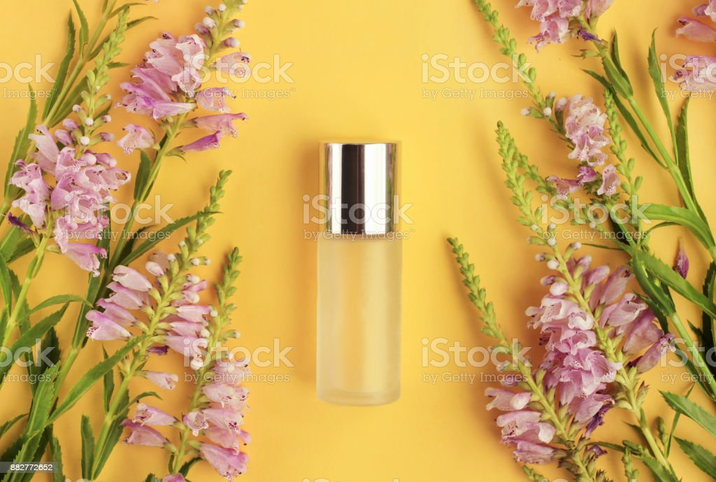 Bottle of skin care product on bright sunny yellow background top viewed, framed aromatic fresh lilac flowers. stock photo
