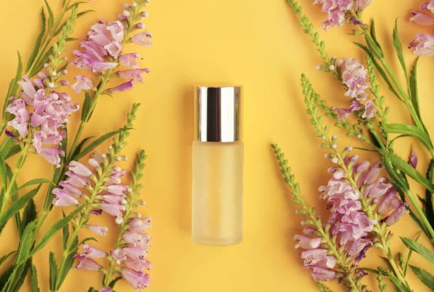 flaska hudvårdsprodukt ljusa soliga gul bakgrund ovanpå tittade på, inramade aromatisk fräsch lila blommor. - summer smell bildbanksfoton och bilder