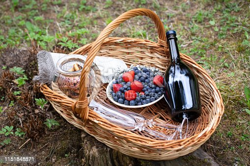 A bottle of sparking wine, berries and cookies in picnic bucket